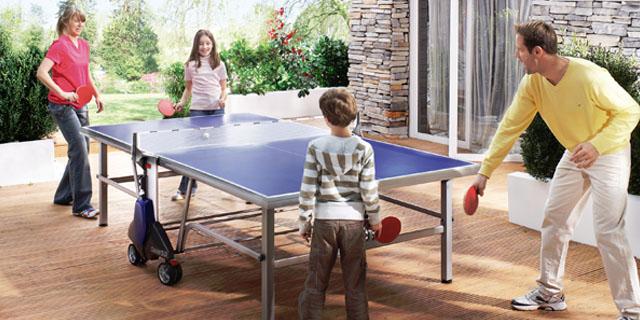familia juagando al ping pong en la tarraza