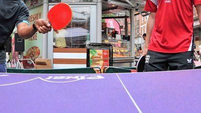chicos jugando al ping pong en la calle