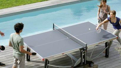 amigos jugando al ping pong junto a la piscina